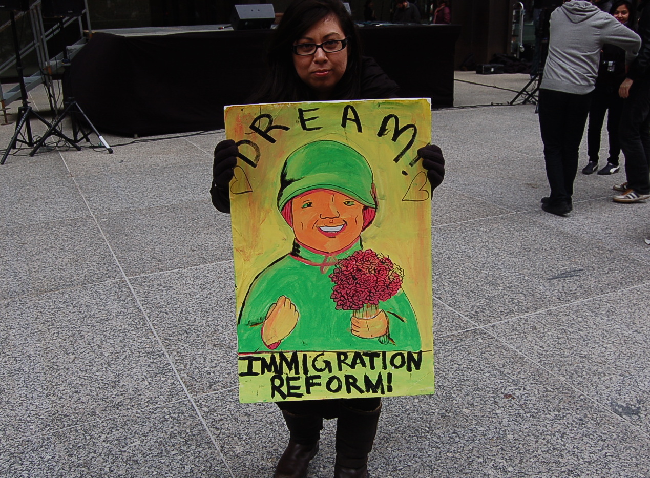"""A protester holds a sign that says \""""dream - immigration reform\"""""""