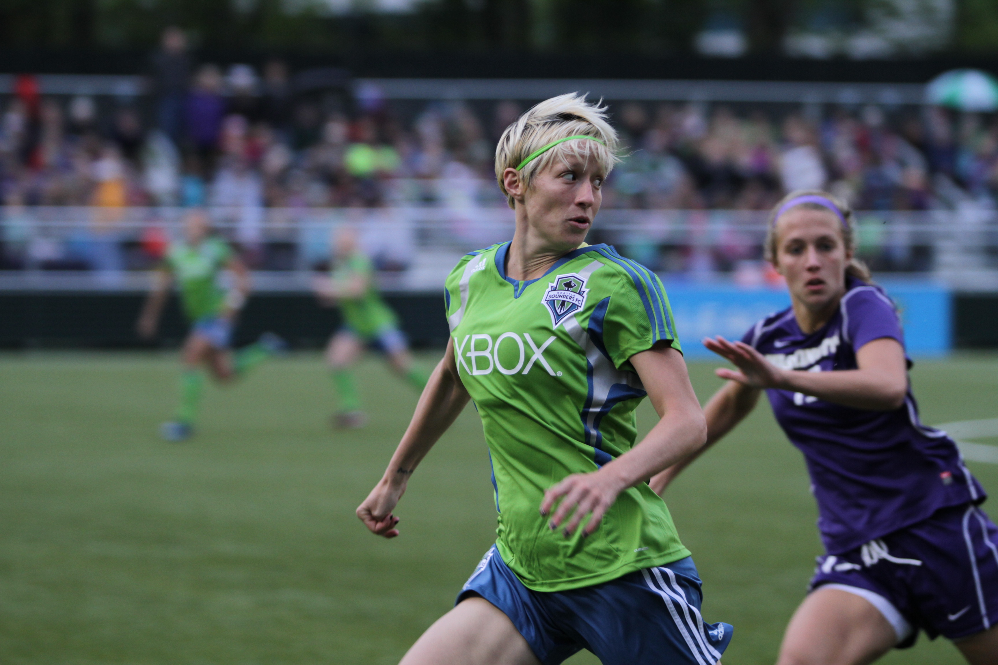 a soccer player with cropped blond hair runs down the field in a lime green shirt