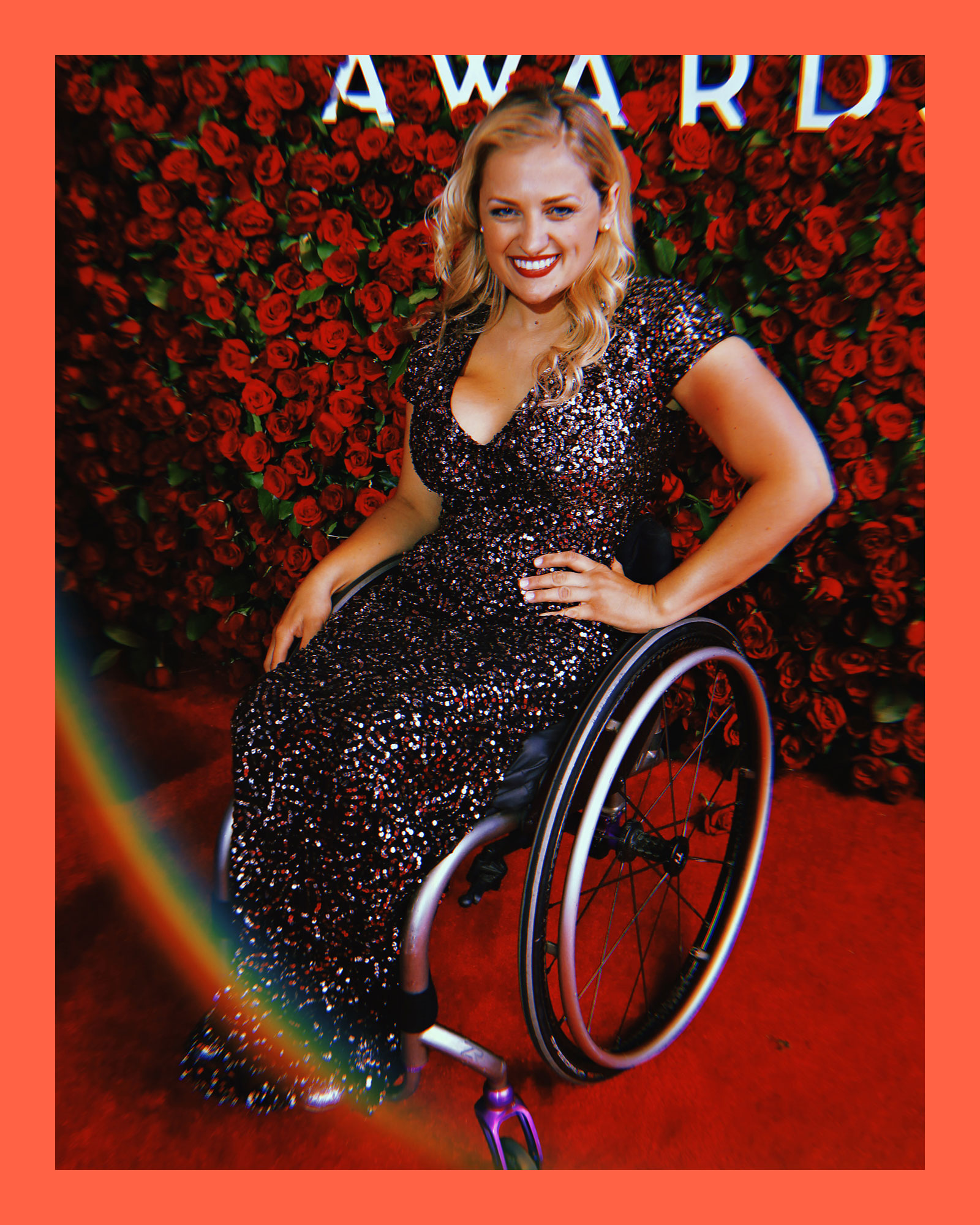 photo of actress Ali Stroker, a white, blonde woman wearing a long, v-neck sequined dress, sitting in her wheelchair on a redcarpet, and smiling in front of a wall of red roses