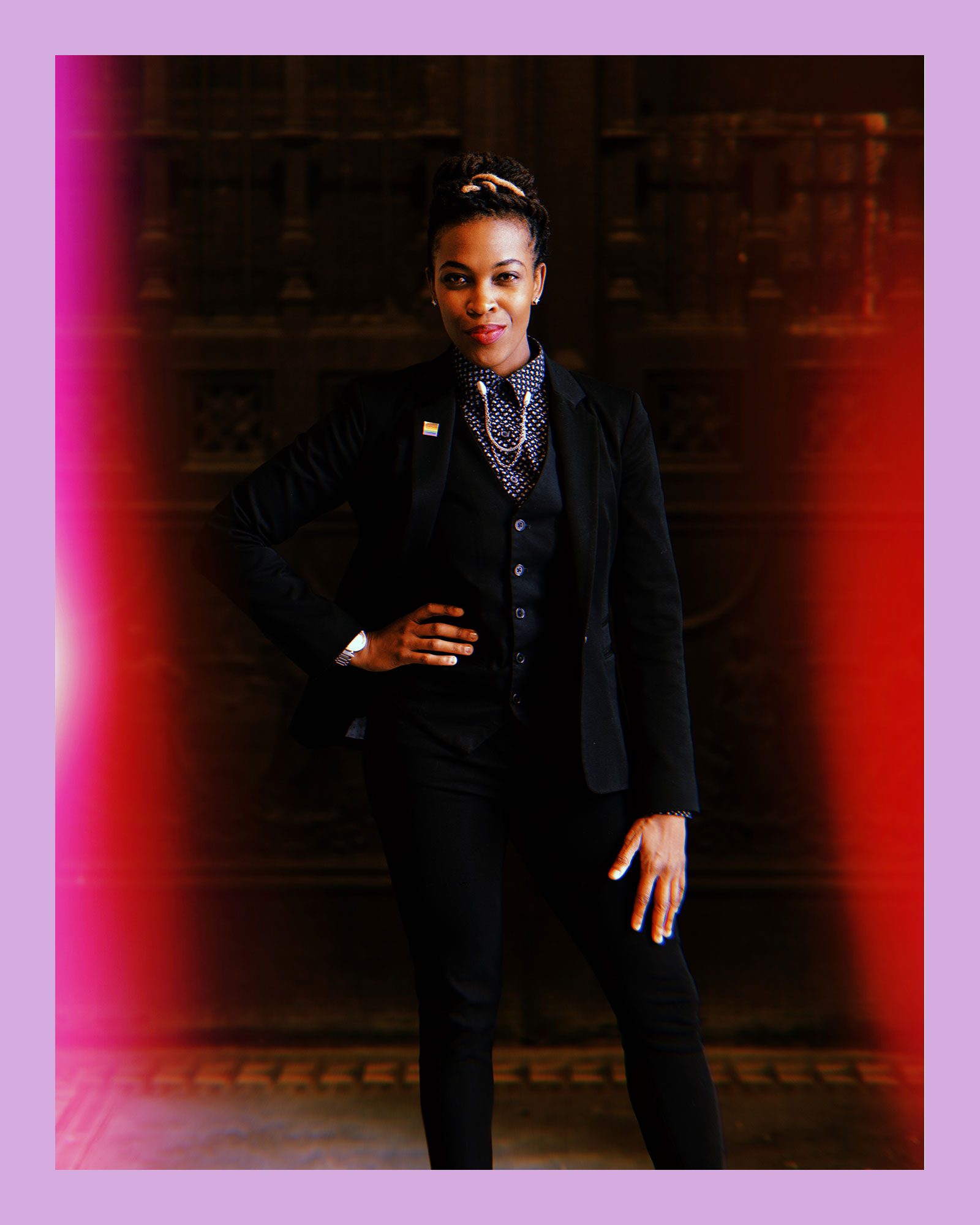 photo of Amber Hikes, a Black woman and Director of Diversity at the ACLU, wearing a 3-piece black suit and blue collared shirt, standing in a historical-looking building.
