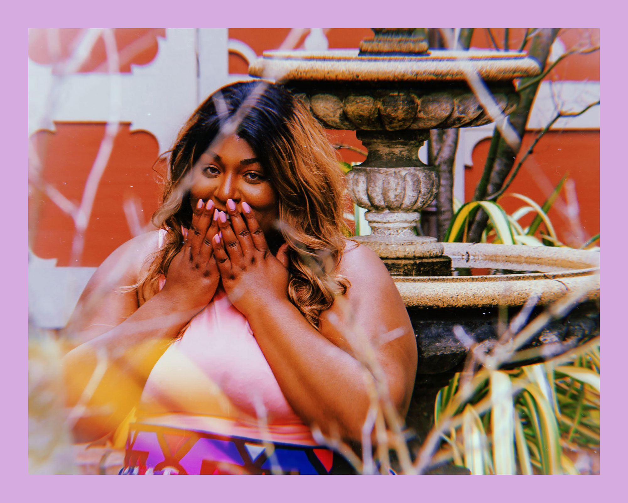 photo of a Black woman and activist, Aria Sa'id, standing outside in front of a fountain, surrounded by greenery, whilewearing a pink top and blue patterned skirt, holding her hands up to her mouth while smiling