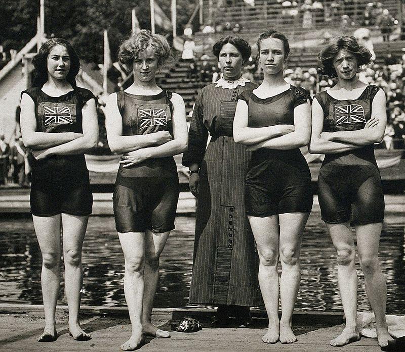 five women stand in front of a swimming pool