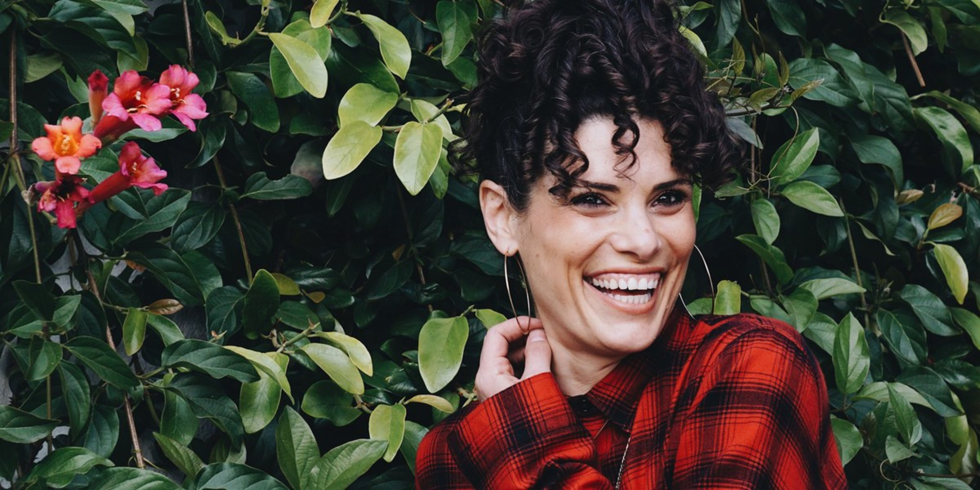 smiling woman in red plaid shirt in front of a bright green hedge