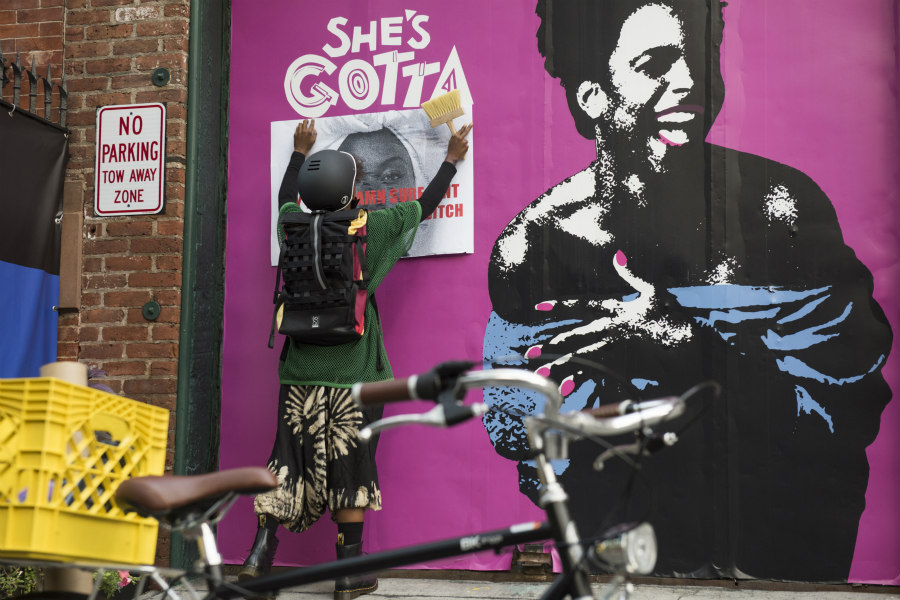 DeWanda Wise as Nola Darling hanging her guerilla art in She's Gotta Have It
