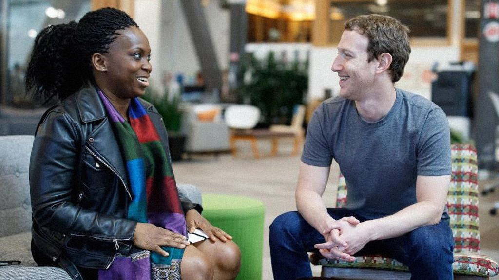 a Black woman in conversation with Mark Zuckerberg, both seated