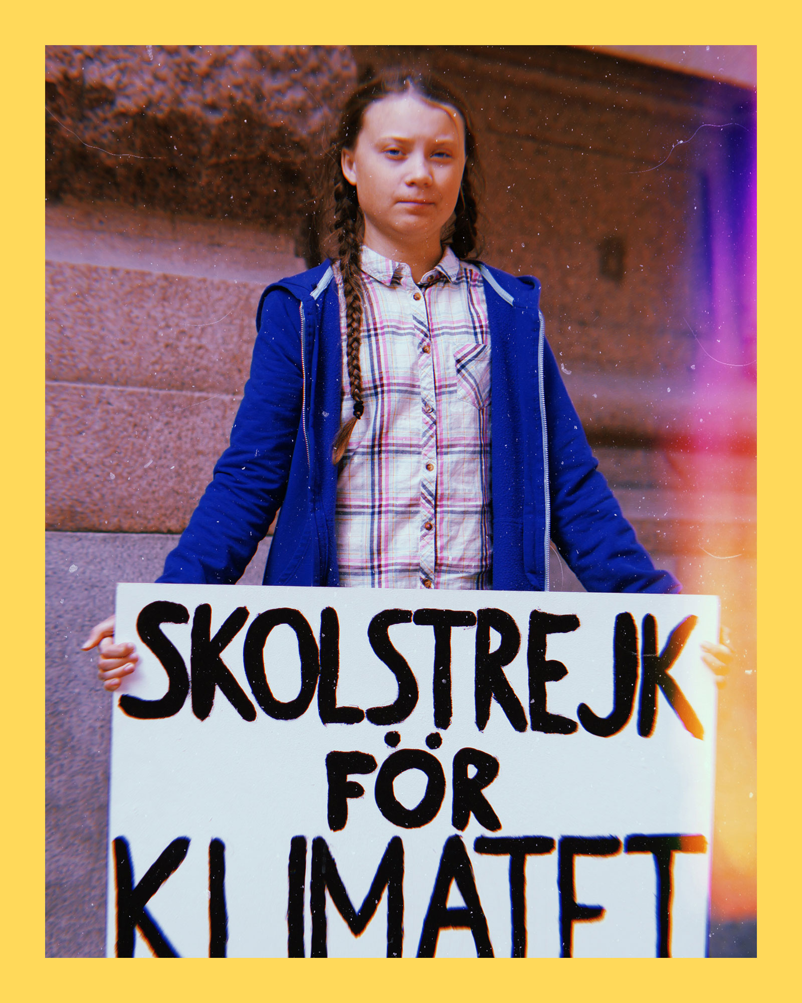 photo of climate activist, Greta Thunberg, standing outside, wearing a blue hoodie and plaid shirt while holding a climate strike poster