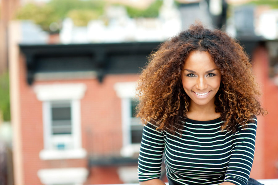 Janet Mock, a transgender Hawaiian woman with curly, brown hair, smiles