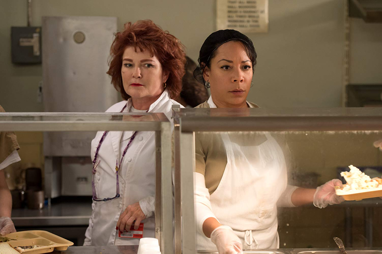a white woman with red hair and a Latina cook together in a prison ktichen