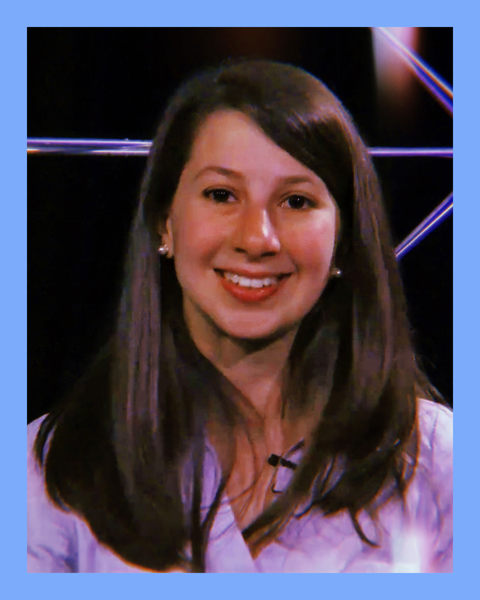 closeup photo of grad student, Katie Bouman, a young white woman with long brown straight hair, wearing a purple top and smiling
