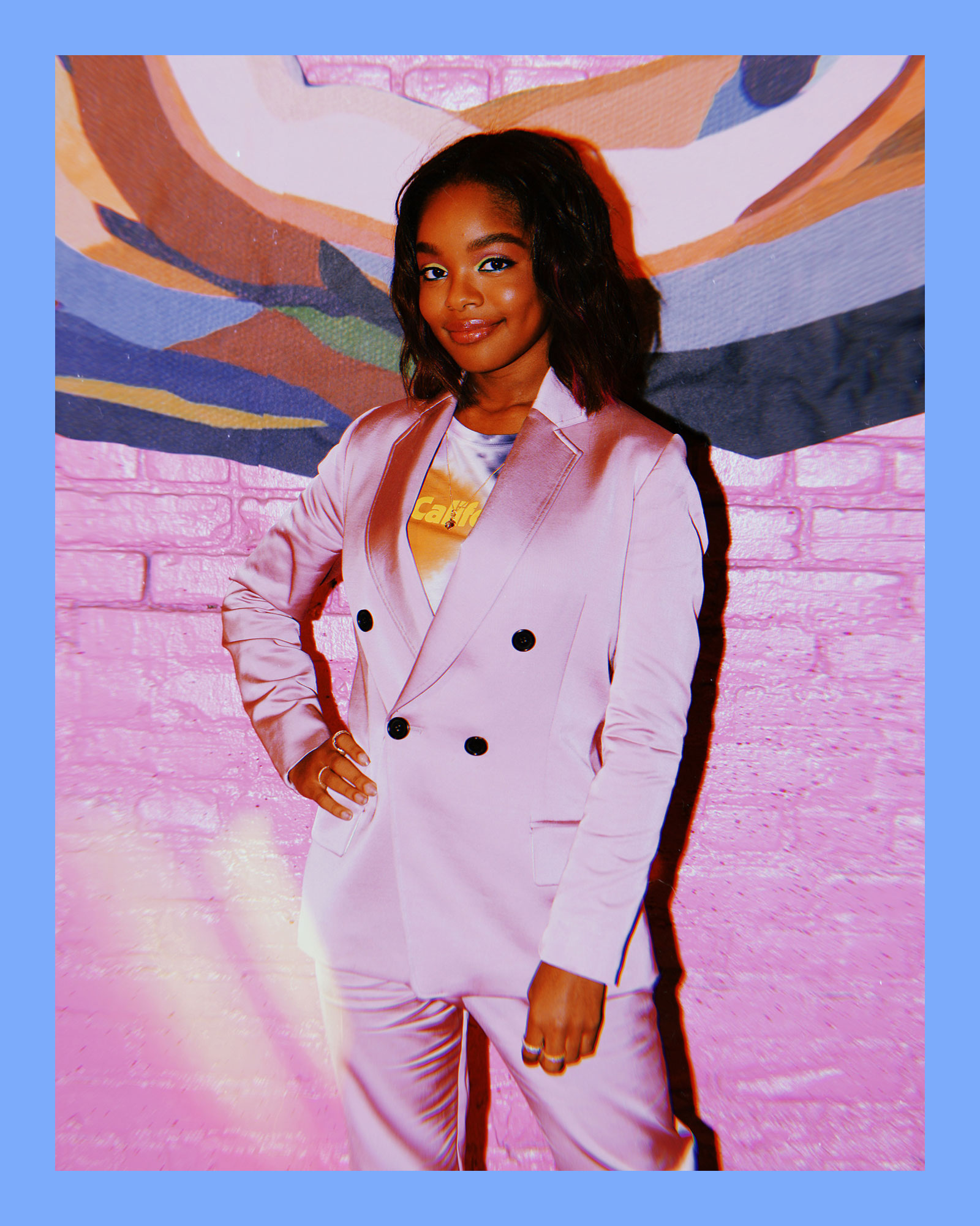 photo of Marsai Martin, an actress, executive producer, and young Black woman wearing a 2-piece pink satin suit, smiling and standing in front of a pink brick wall.