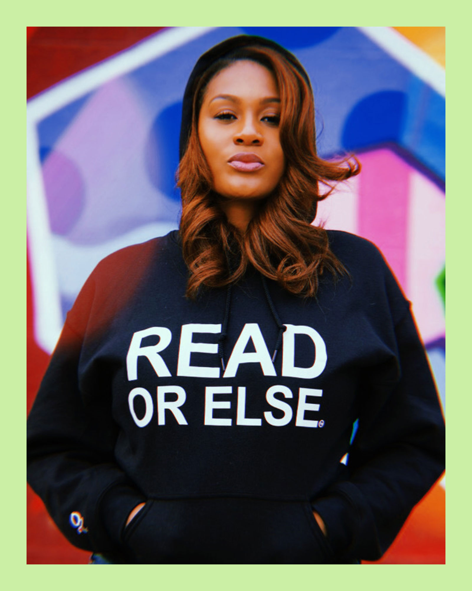 "photo of Lit.Bar founder, Noëlle Santos, an Afro Latina woman with long brown curled hair, standing in front of a colorful mural, wearing a black hoodie with the words ""Read or else"""