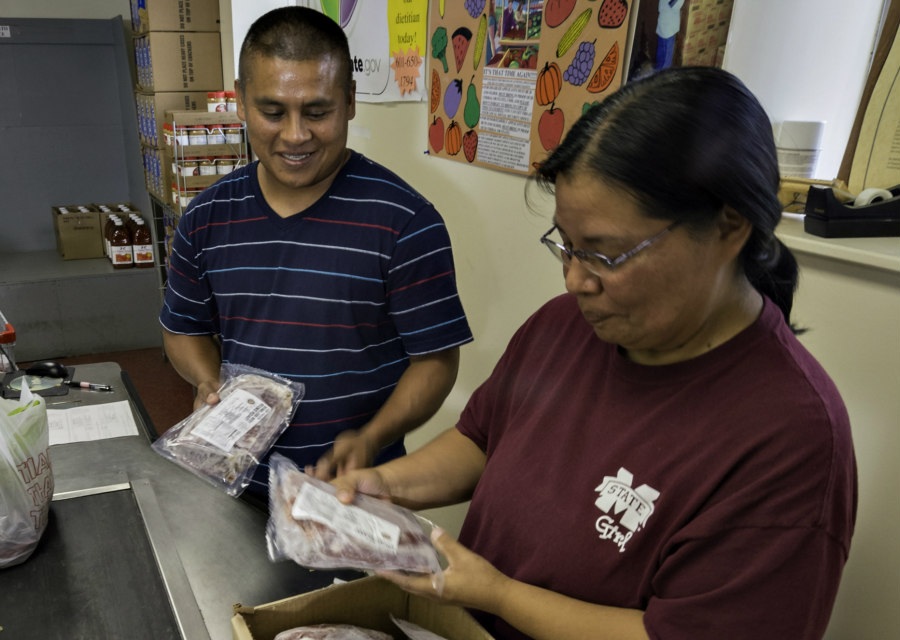 Ricky John and Anita Frazier pack food for a family in the Choctaw Nation Food Distribution Program on Indian Reservations site in Choctaw, MS