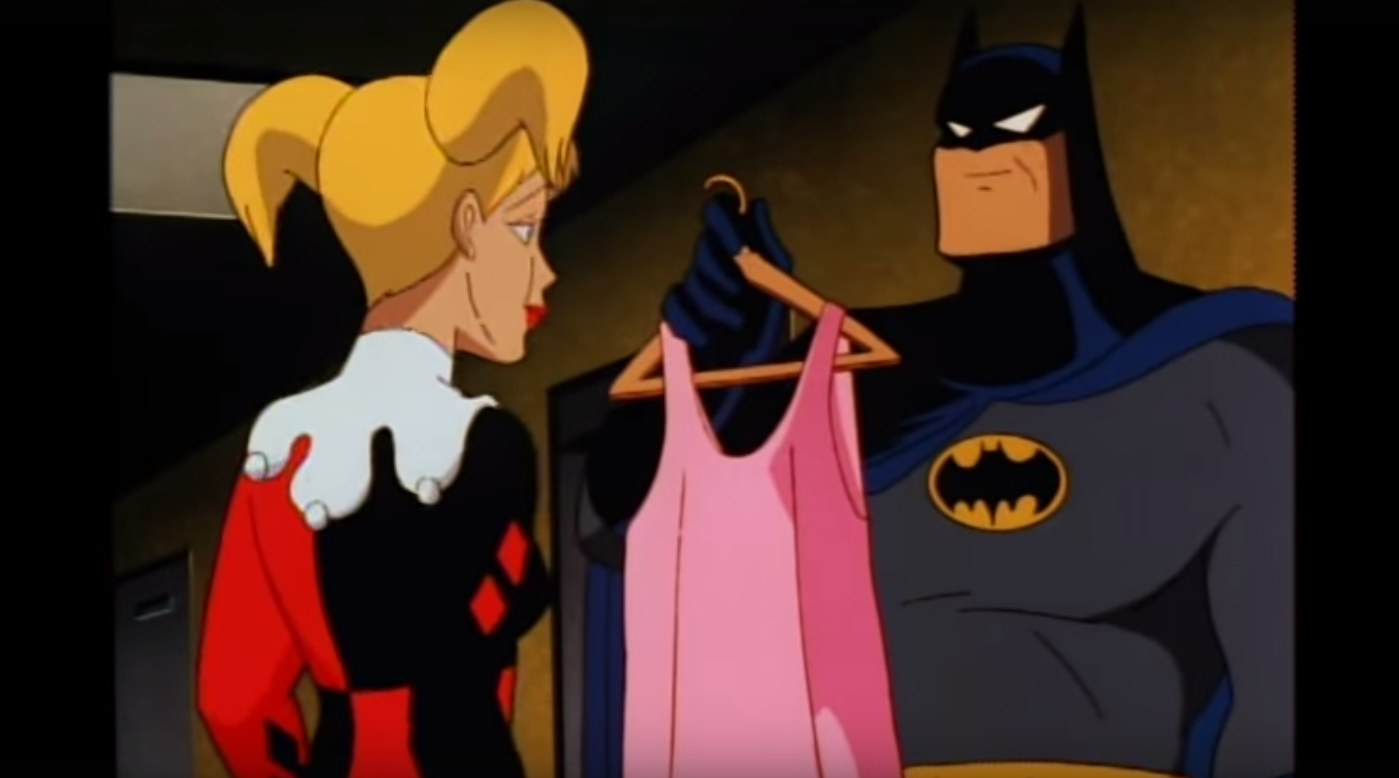 Harley accepting a pink dress as a gift from Batman.