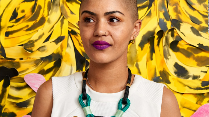 a young south african woman stands in front of a painting of bananas