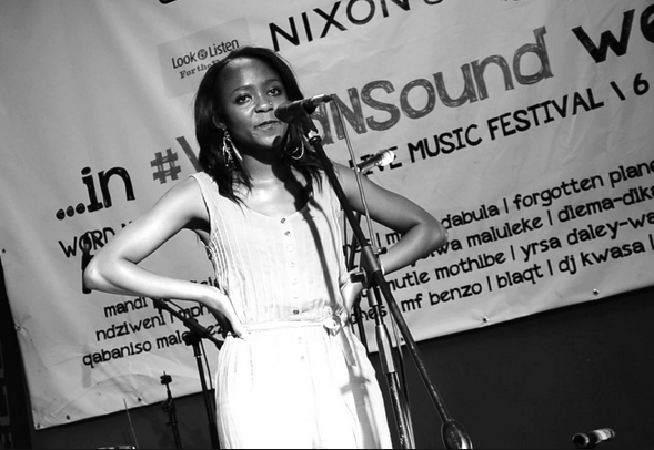 A young Black woman in a light dress stands in front of a mic on stage, hands on hips