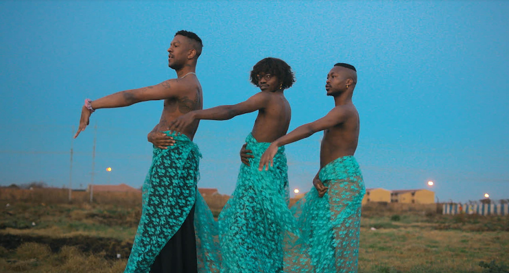 Three black figures in turquoise lace sarongs strike a pose against a bright blue sky