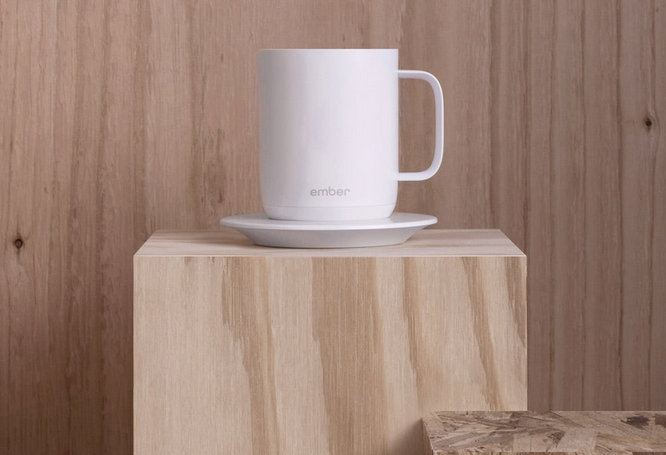 streamlined white ceramic mug sits atop a wooden pillar