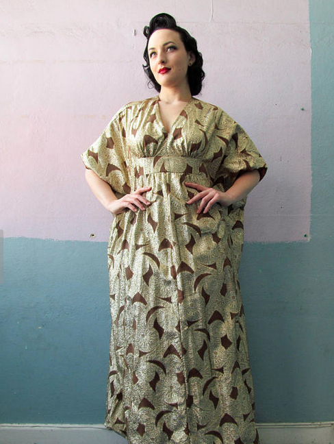 white woman with retro updo poses in vintage gold-and-brown caftan