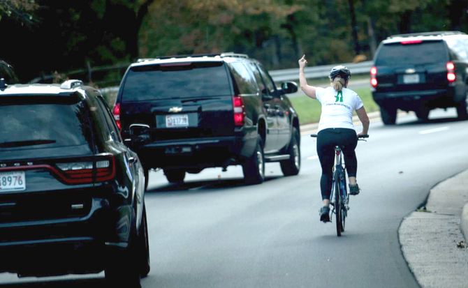 the backs of three black cars at left; at right, a woman on a bicycle raises her middle finger