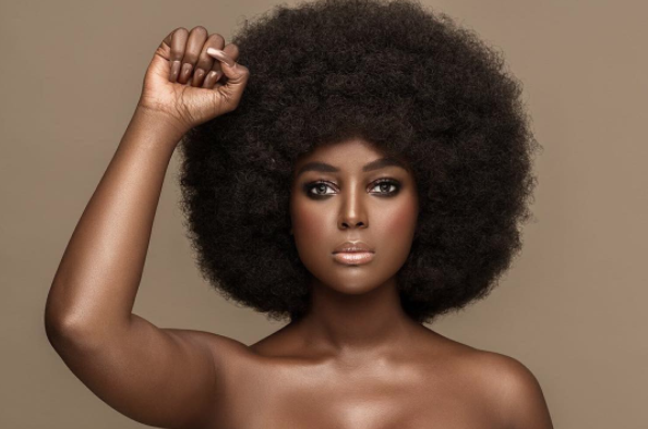 Amara La Negra, a dark-skinned Afro Latinx woman in afro, faces forward with her fist raised