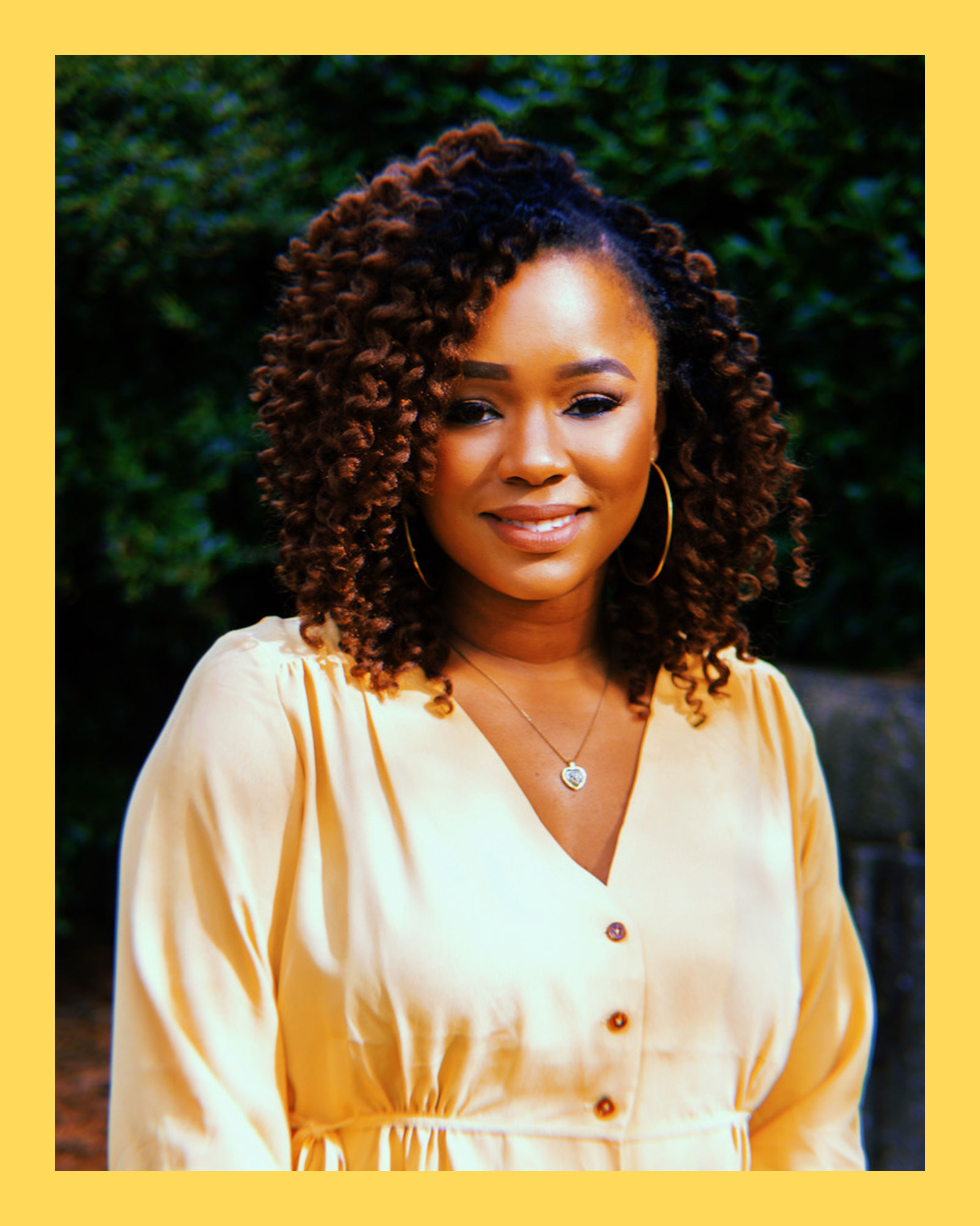 photo of journalist and social entrepreneur, Sherrell Dorsey, a Black woman with brown curly hair, wearing a yellow, long sleeved blouse, hoop earrings and necklace, standing outside smiling