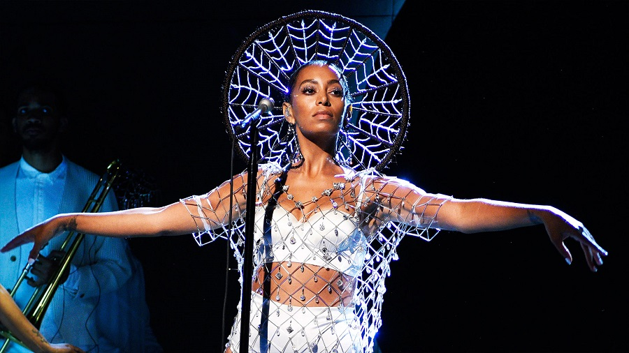 Solange Knowles wearing a crown with her arms outstretched during a performance
