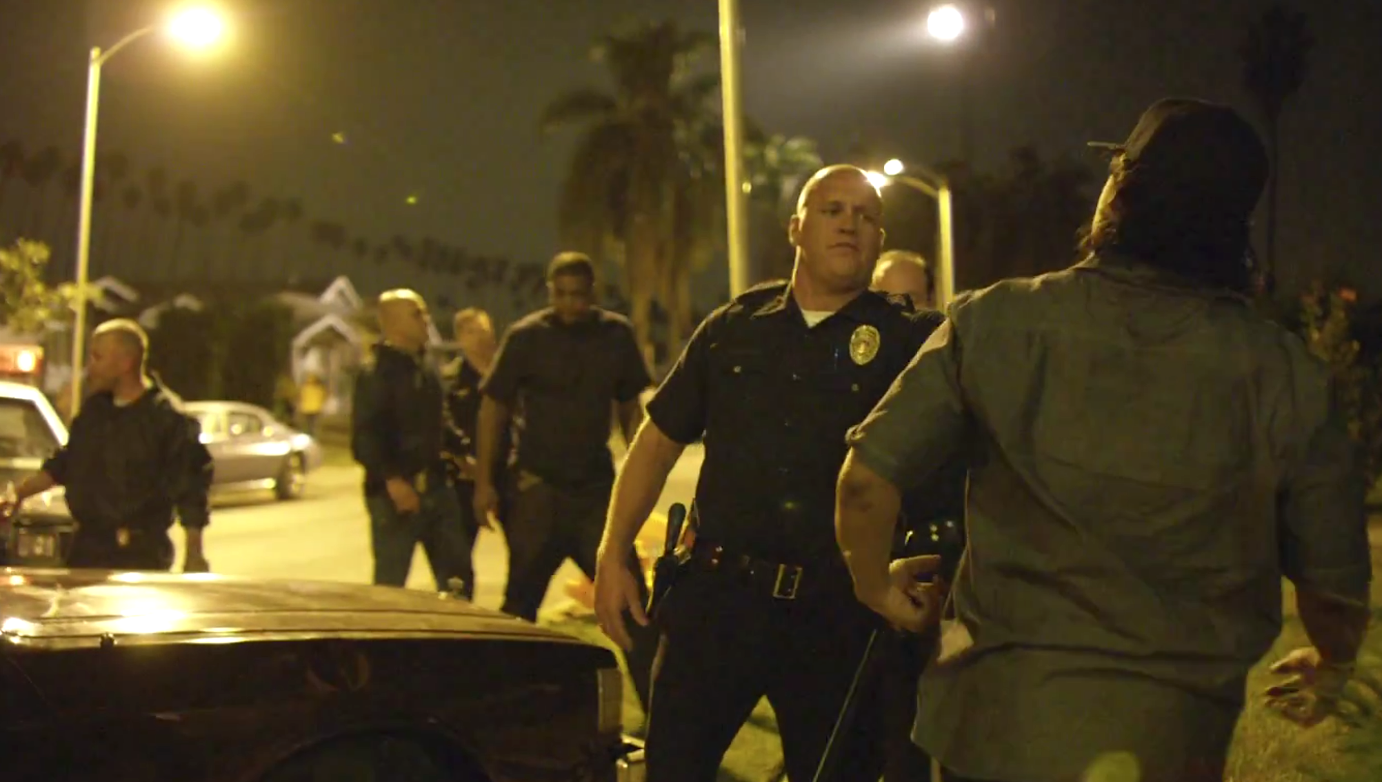 Police and members of NWA glare at each other in a scene from Straight Outta Compton