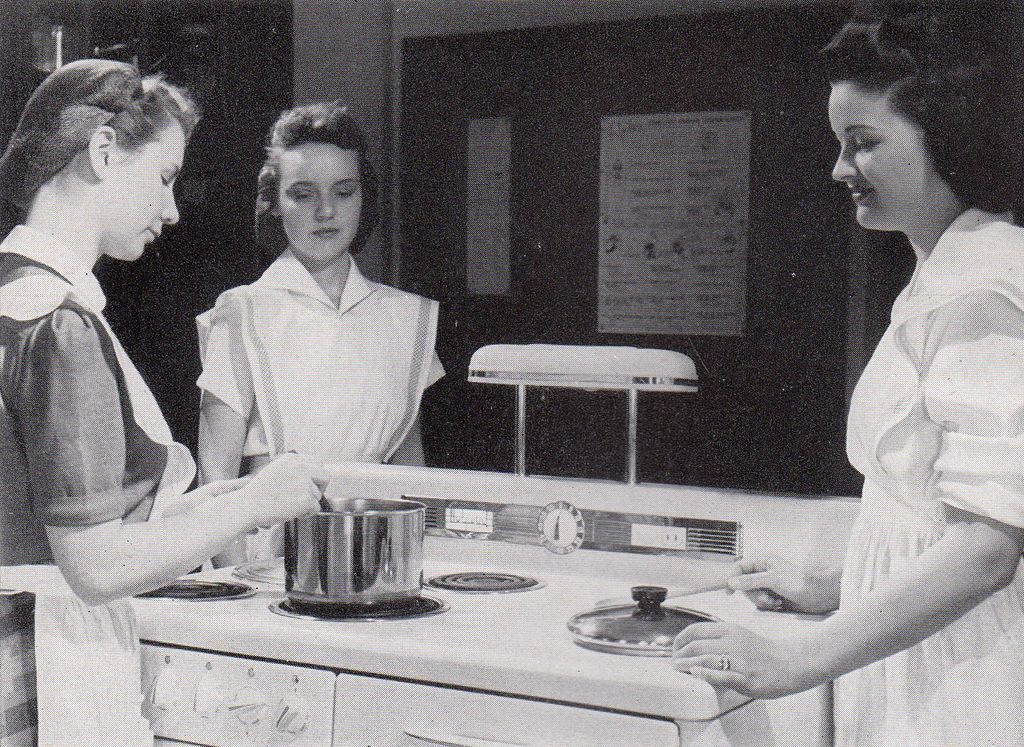 a black and white photo of three female students at Shimer College taking a home economics class in 1942