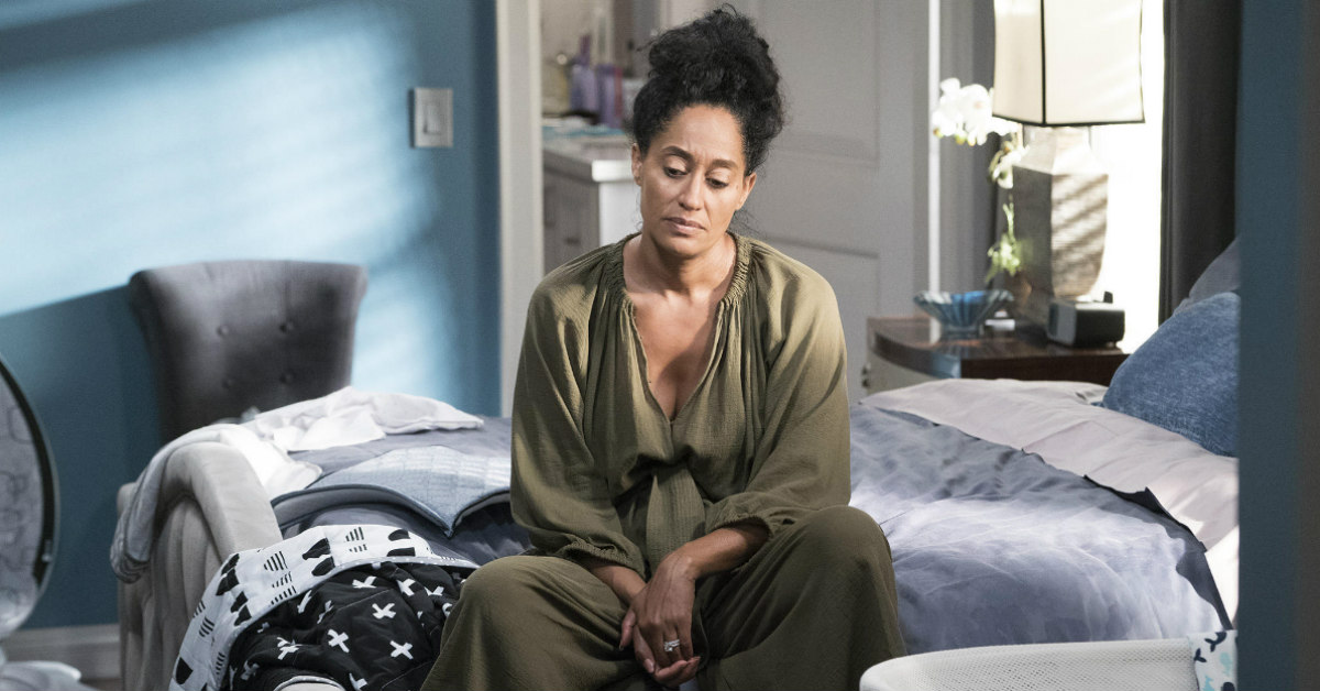 a lightskinned Black woman with an afro sits on a bed, looking depressed