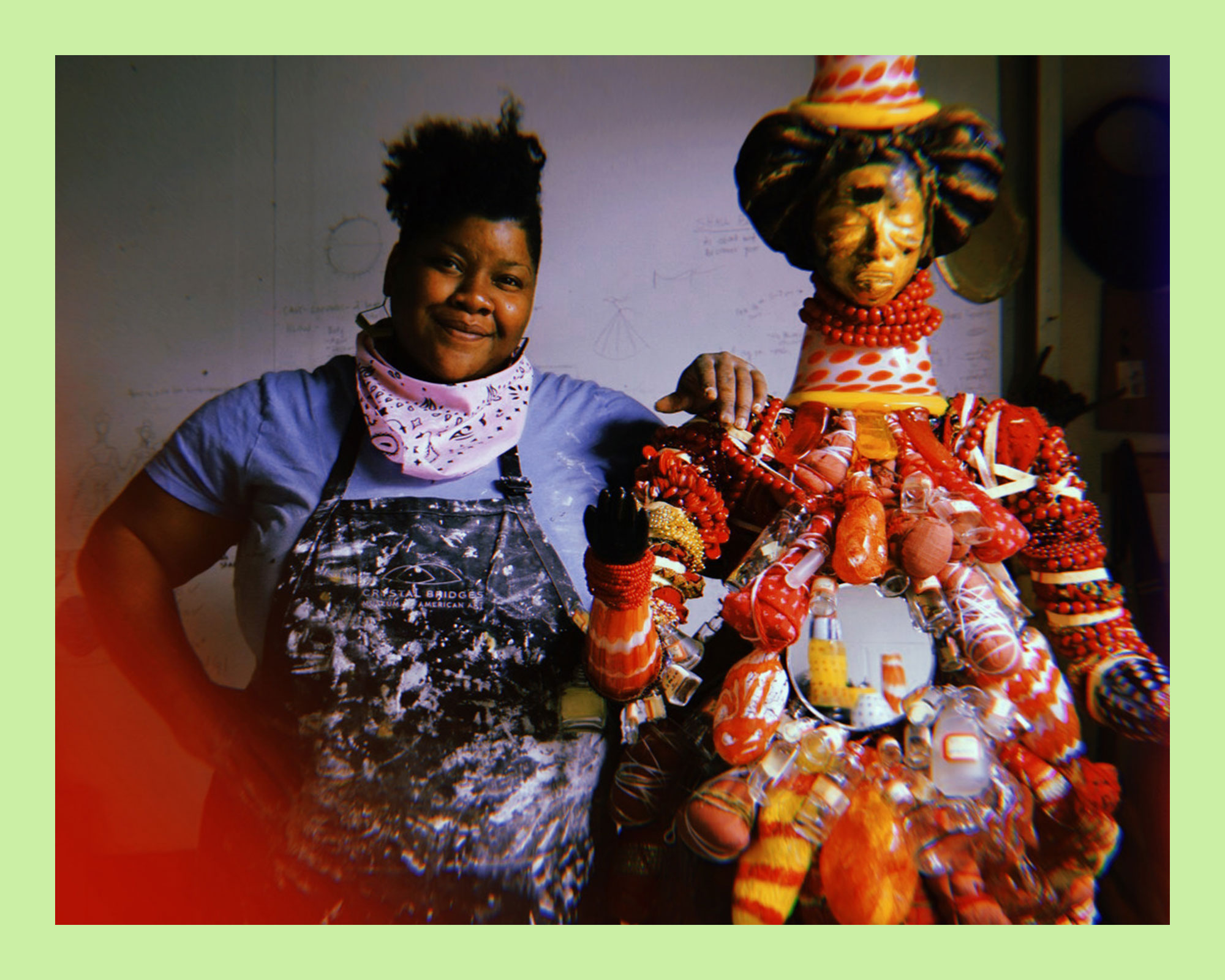 photo of a Black woman and artist, Vanessa German, smiling and standing next to her mixed-media sculpture