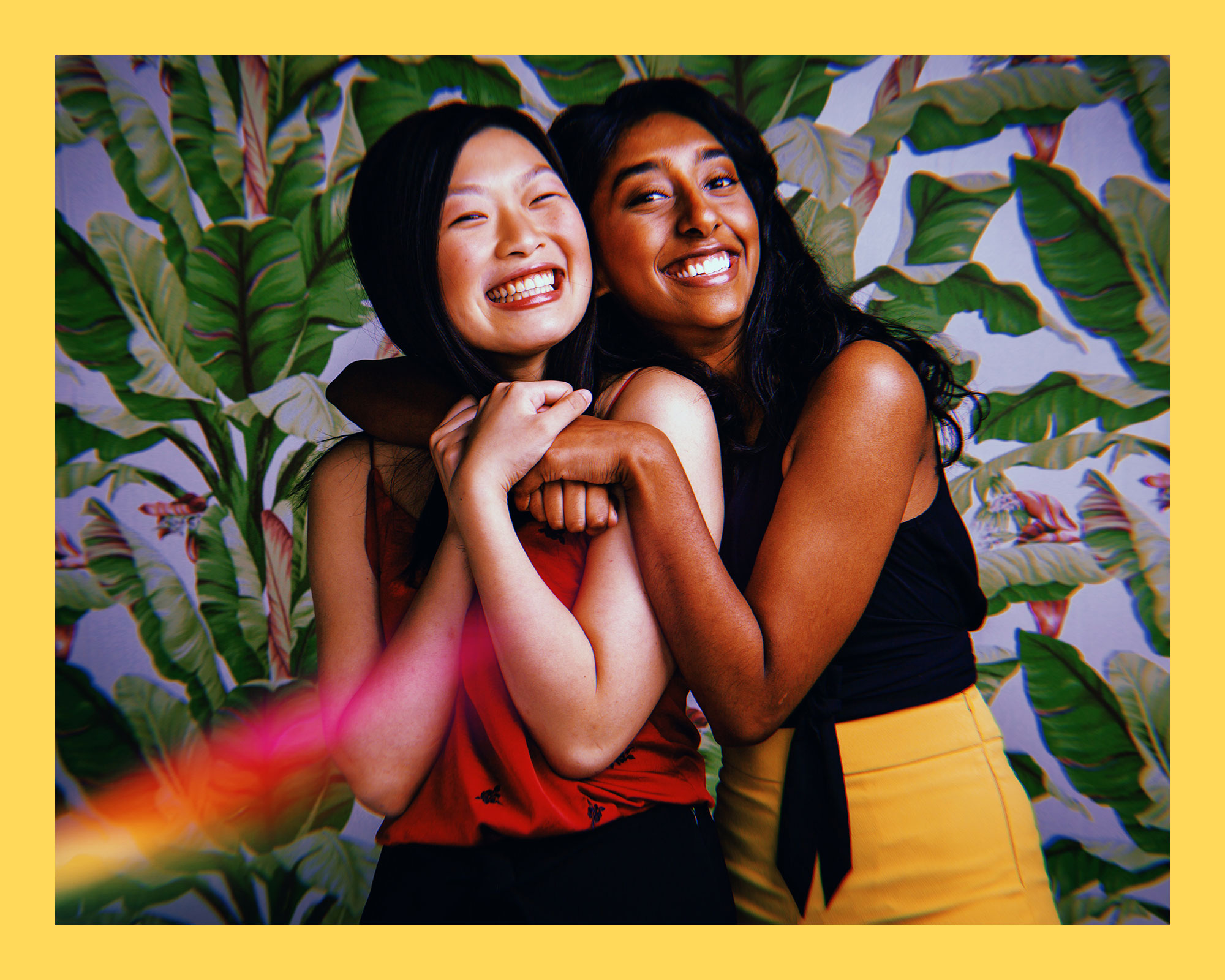 photo of two Asian women in a side-by-side embrace, smiling in front of a palm leaf-patterned wall
