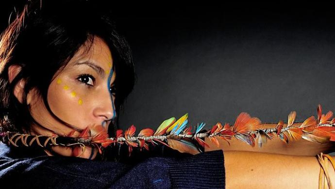A photo of Ana Tijoux, a Chilean woman stretching her arm horizontally holding a feathered string attached to her hair.