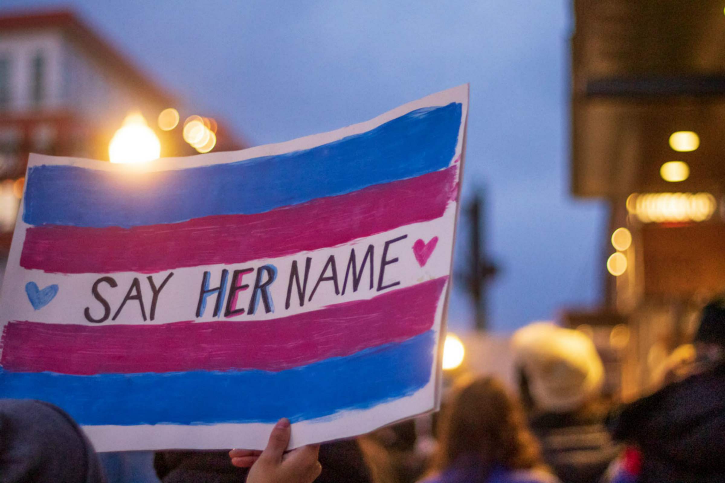 a white hand holds a white, blue, and dark purple #SayHerName sign surrounded by a blue and a purple heart during a march