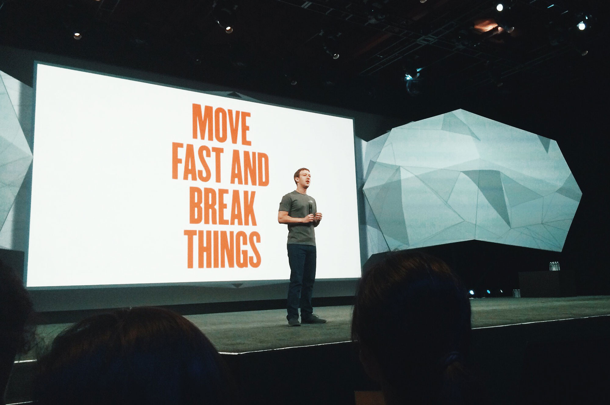 a white man stands in front of a large screen that says move fast and break things in orange