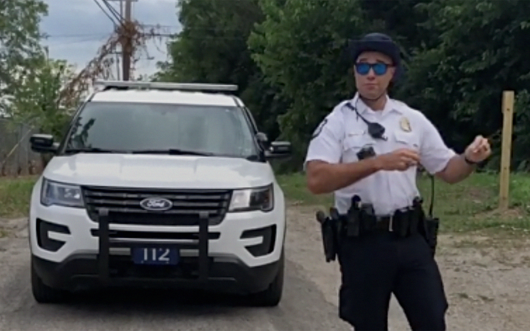 A photo of Officer Anthony Johnson (@ohnoitsdapopo) on TikTok. He is dancing in front of his cop car while in uniform.