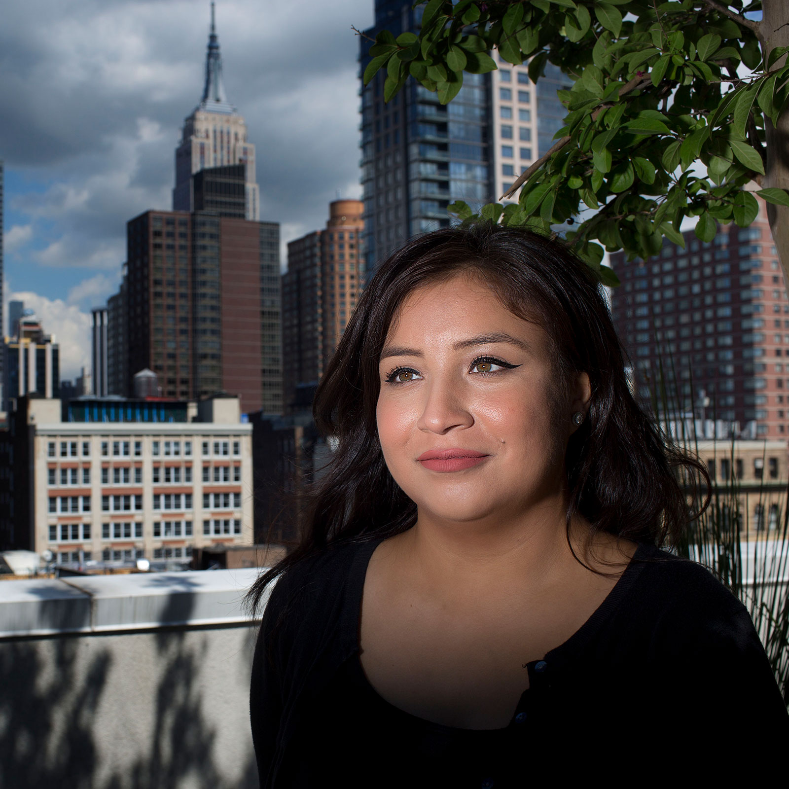 Dior Vargas stands for a portrait on the roof of her parents' apartment in Chelsea.