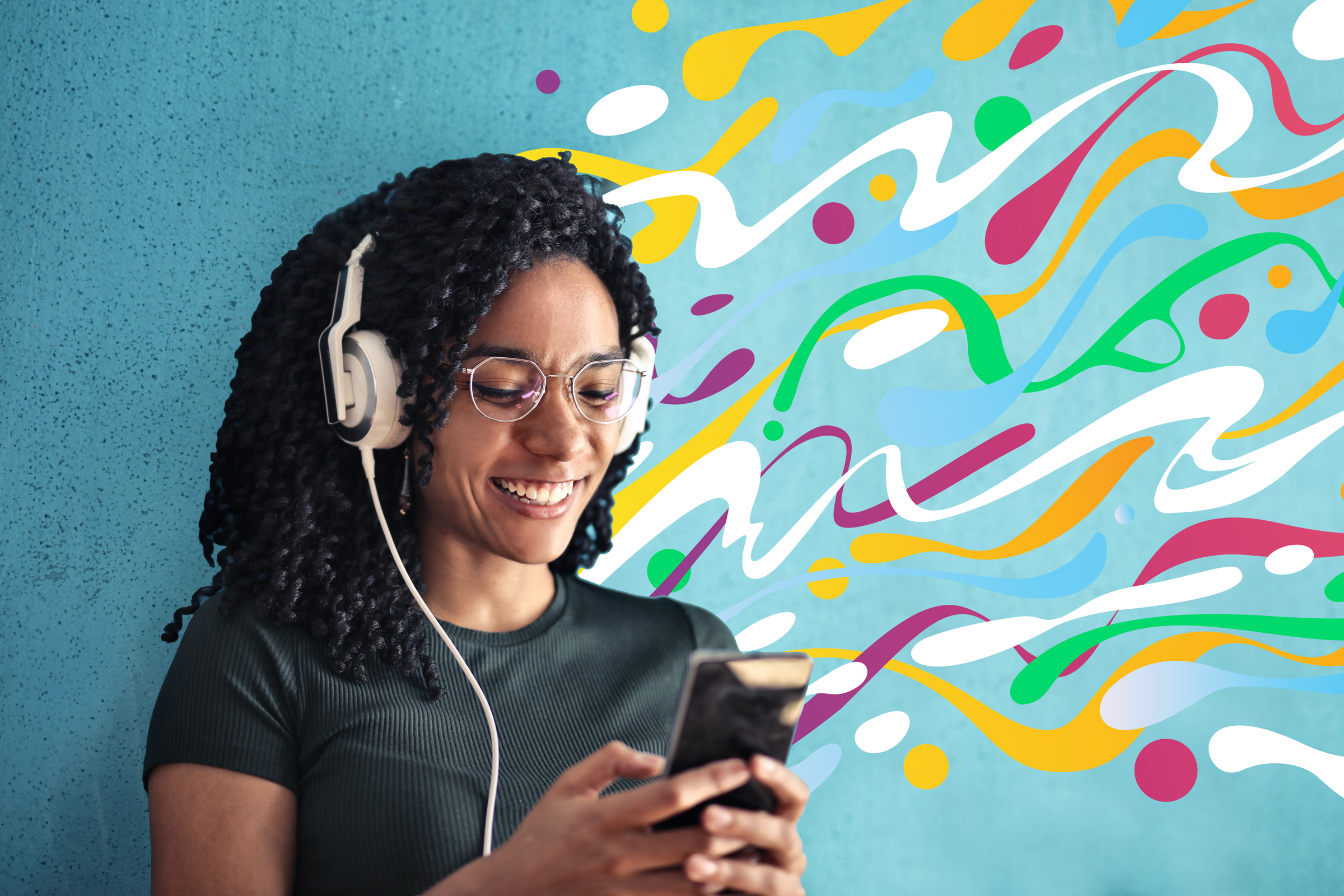 A Black woman with curly hair and glasses smiles at her phone with over the year headphones on.