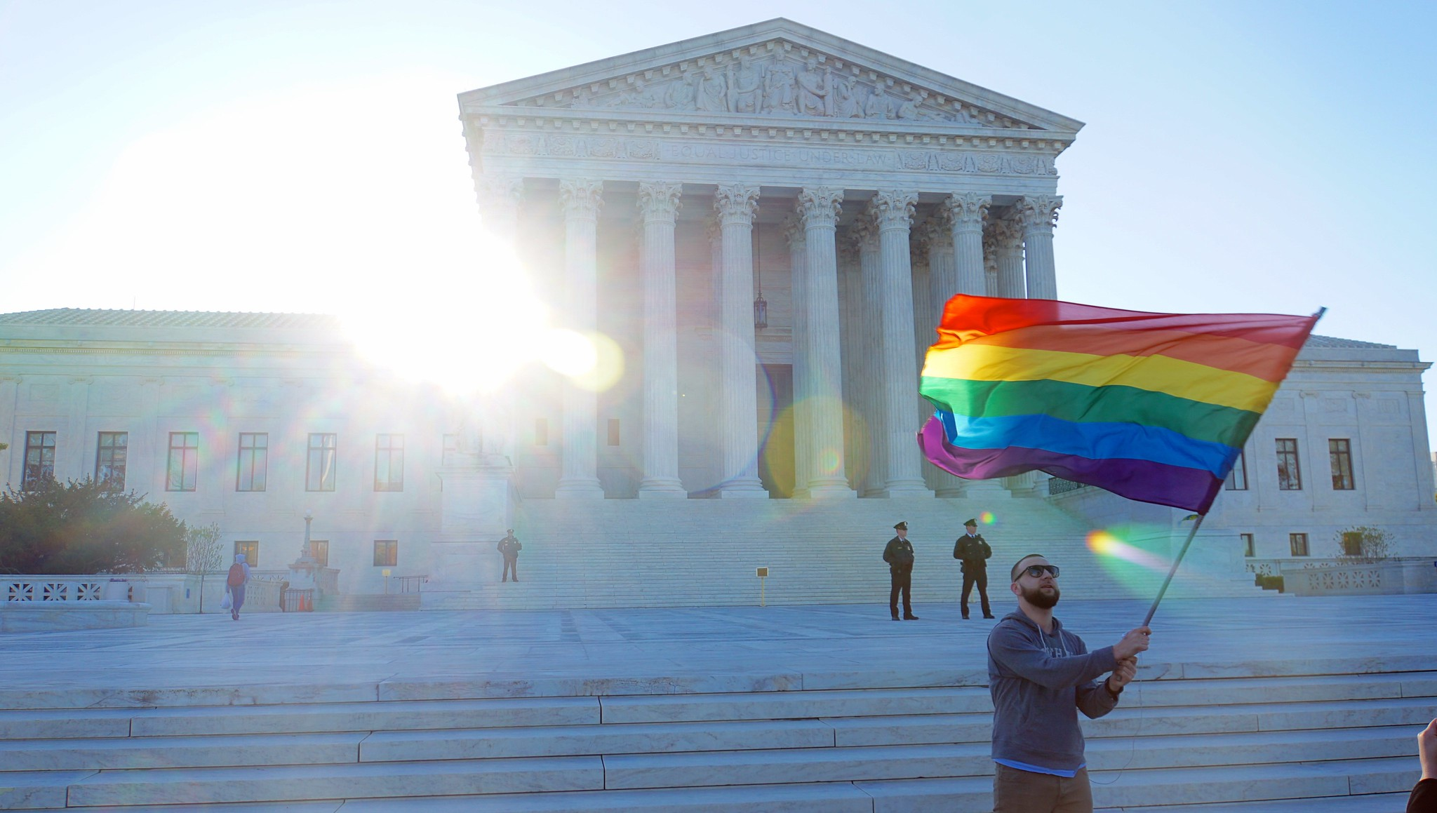 a man stands in front of the U.S. Supreme Court with a LGBTQ flag on April 28, 2015