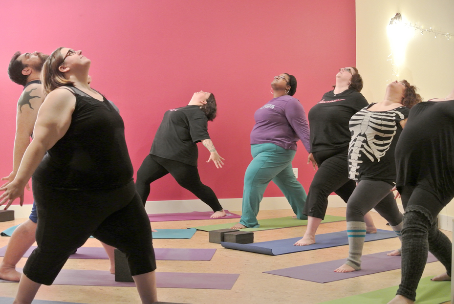 Students in a fat yoga class gaze upwards