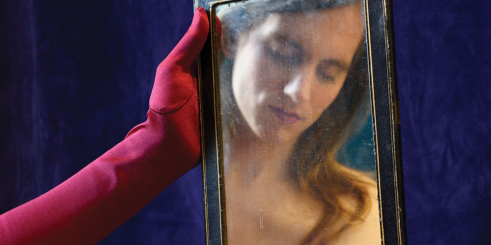 Ana Valens reflected in a mirror being held by hands wearing red opera gloves