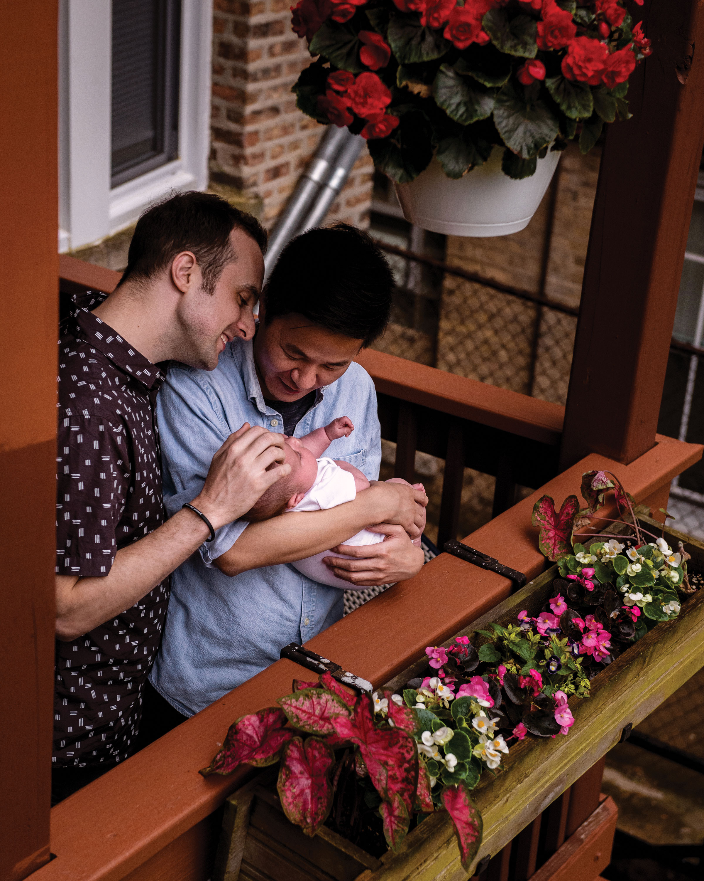 photo of husbands Tyler Greene (left) and Ziwu Zhou (right) and son Sam on their porch