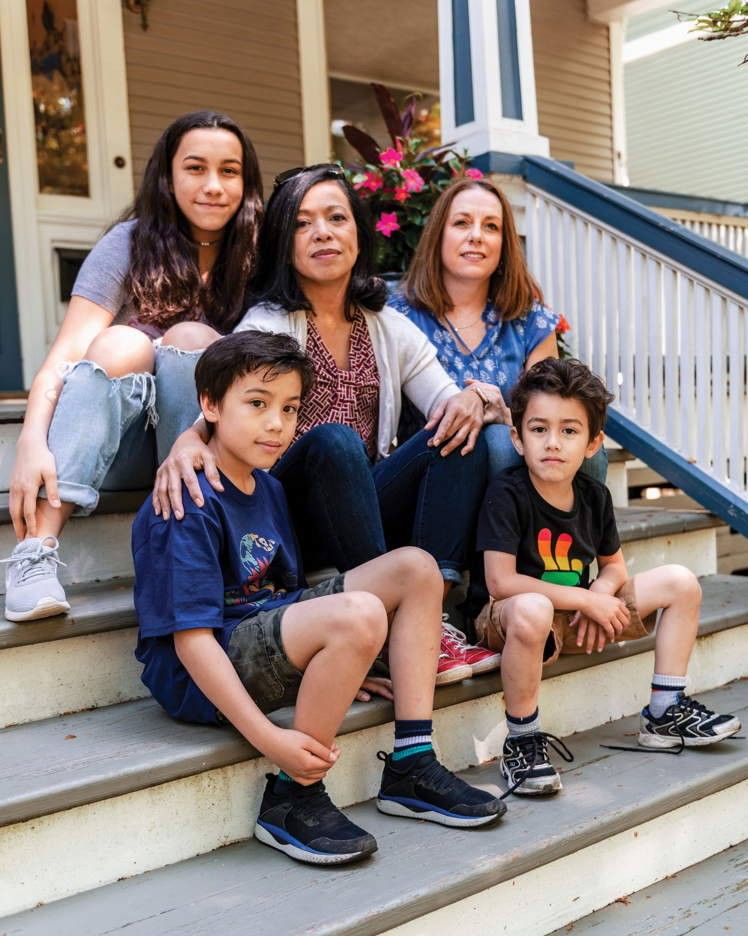 photo of parents Mercedes Santos and Theresa Volpe with their children Ava, Jaidon, and Lennox on their front stoop