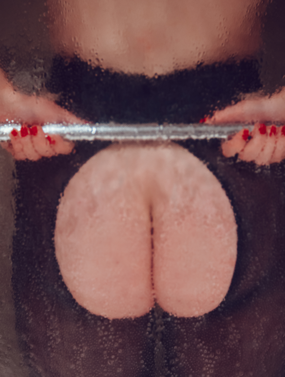 a close-up, soft focus portrait of author Caroline Reilly's buttock holding the bar in her shower
