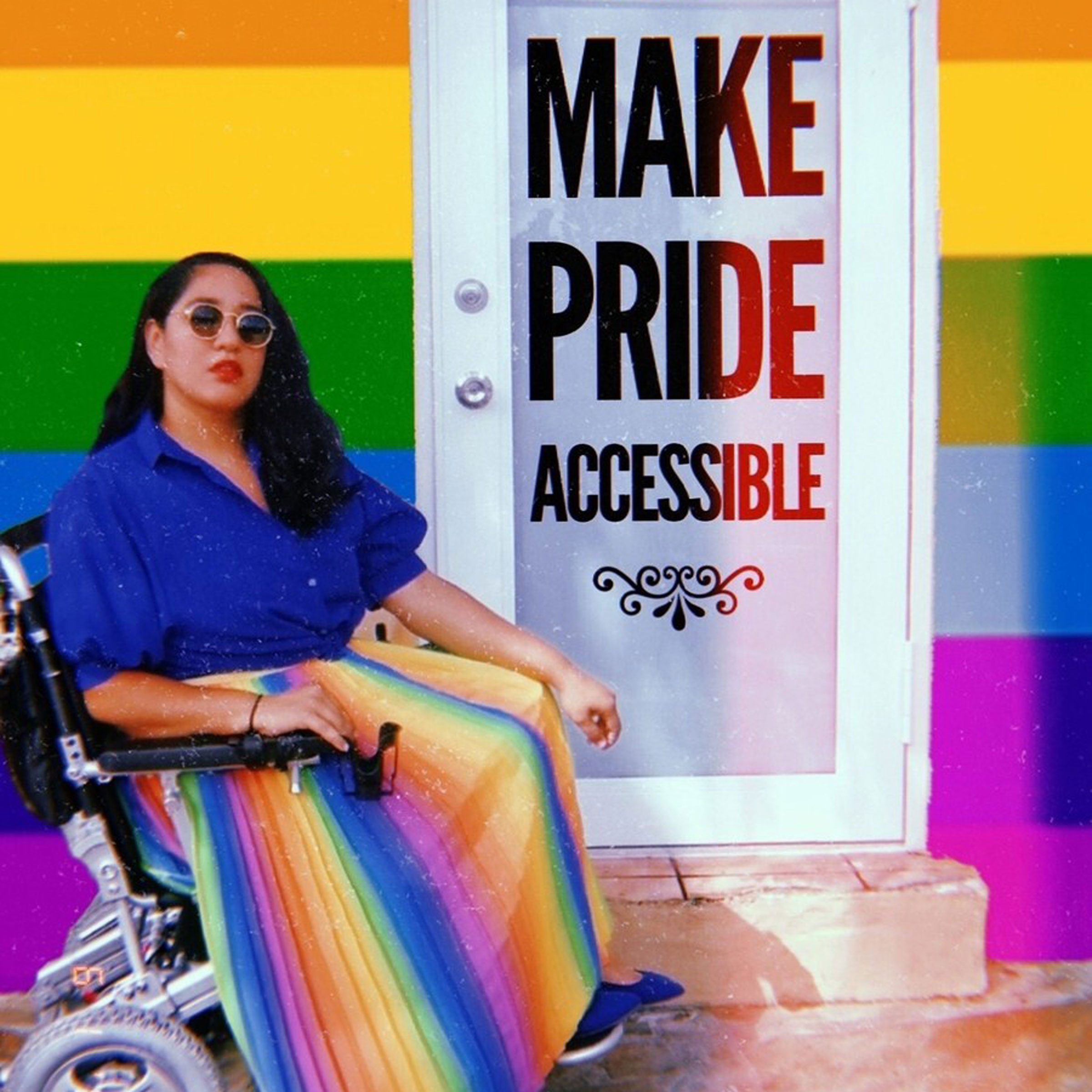 """Photo of Annie Segarra, an American YouTuber, artist, and activist for LGBTQ and disability rights, in a wheelchair wearing a rainbow skirt next to a doorstep and door that reads Make Pride Accessible"""""""