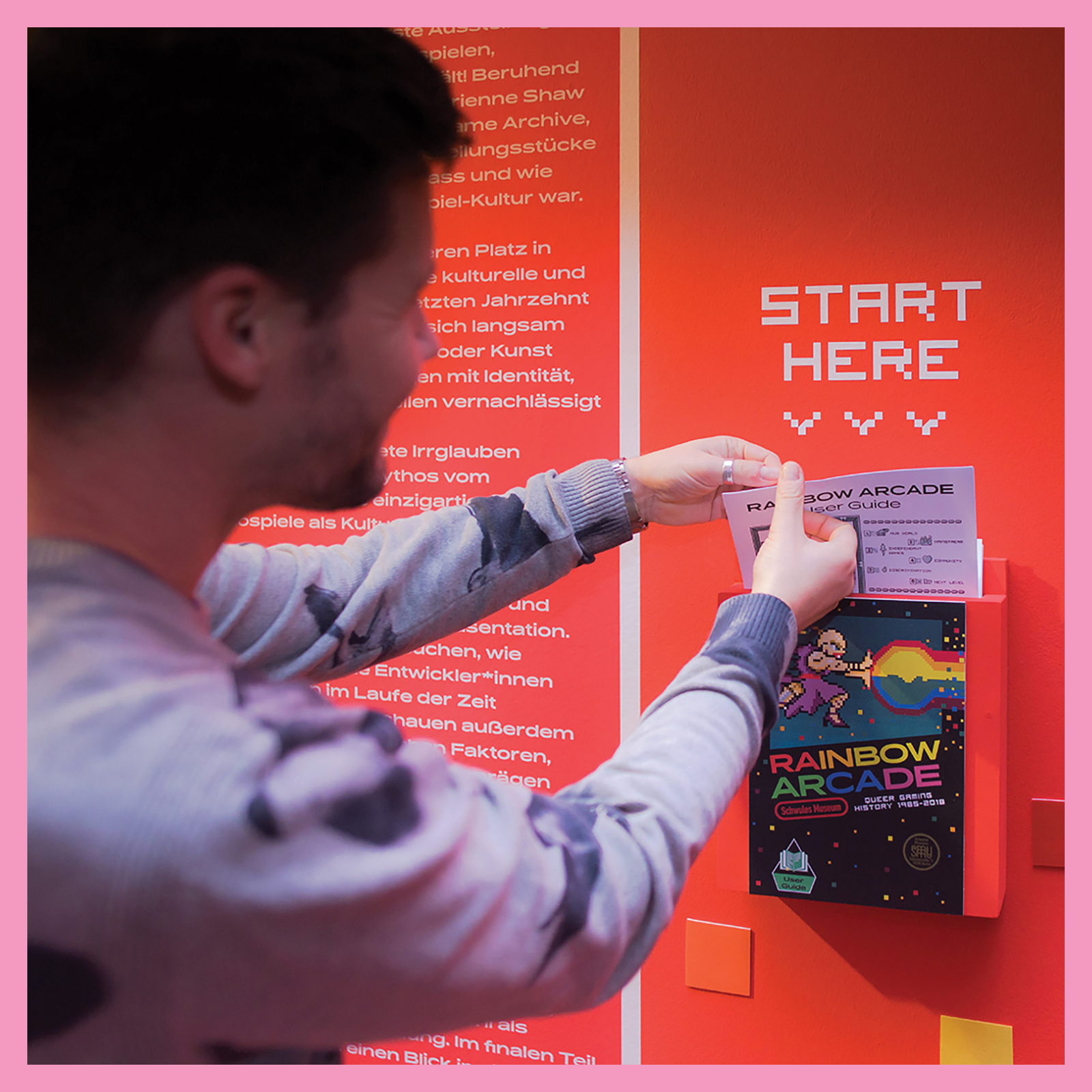 """photo of person grabbing reading material at the exhibition of """"Rainbow Arcade"""" at the Schwules Museum, Berlin."""