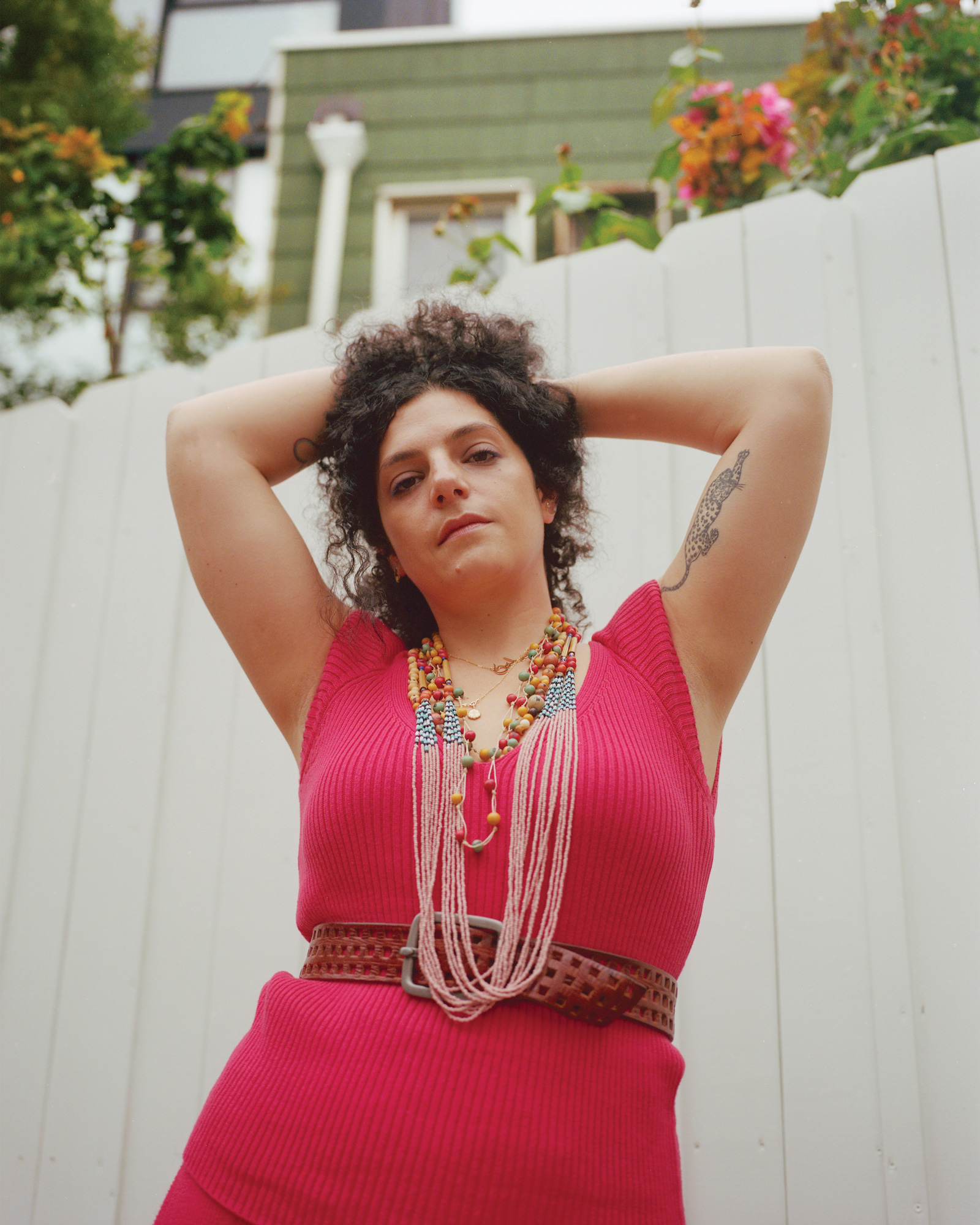 photo of Slow Factor founder, Céline Semaan, a Lebanese Canadian woman posing outside in front of a white fence, wearing a red knitted dress, colorful layered necklaces, and a brown belt, with her arms raised and resting behind her dark curly hair.