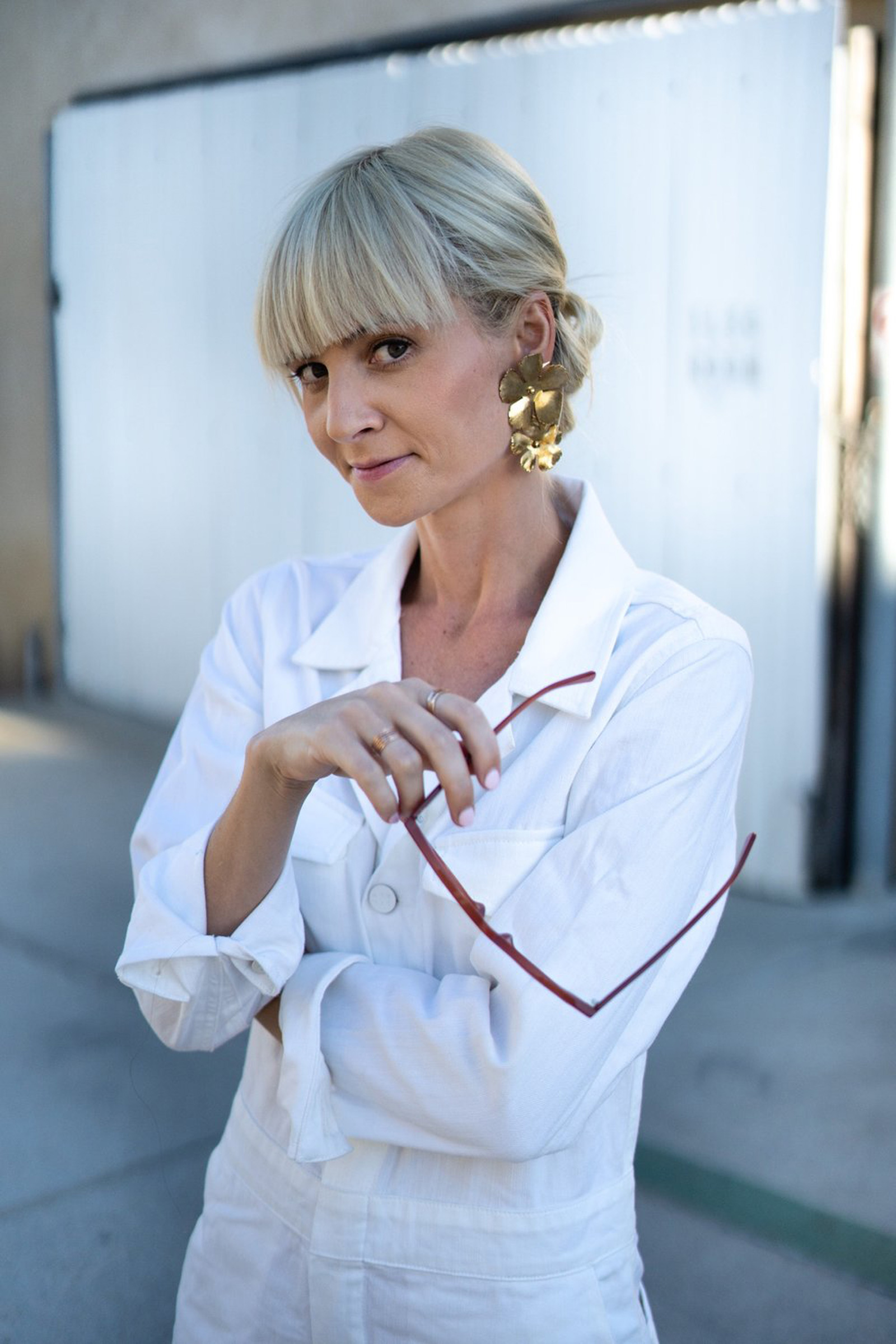 photo of Kestrel Jenkins, a blonde, white woman and host of Conscious Chatter, wearing a white shirt and large gold earrings, standing outside and holding a pair of glasses