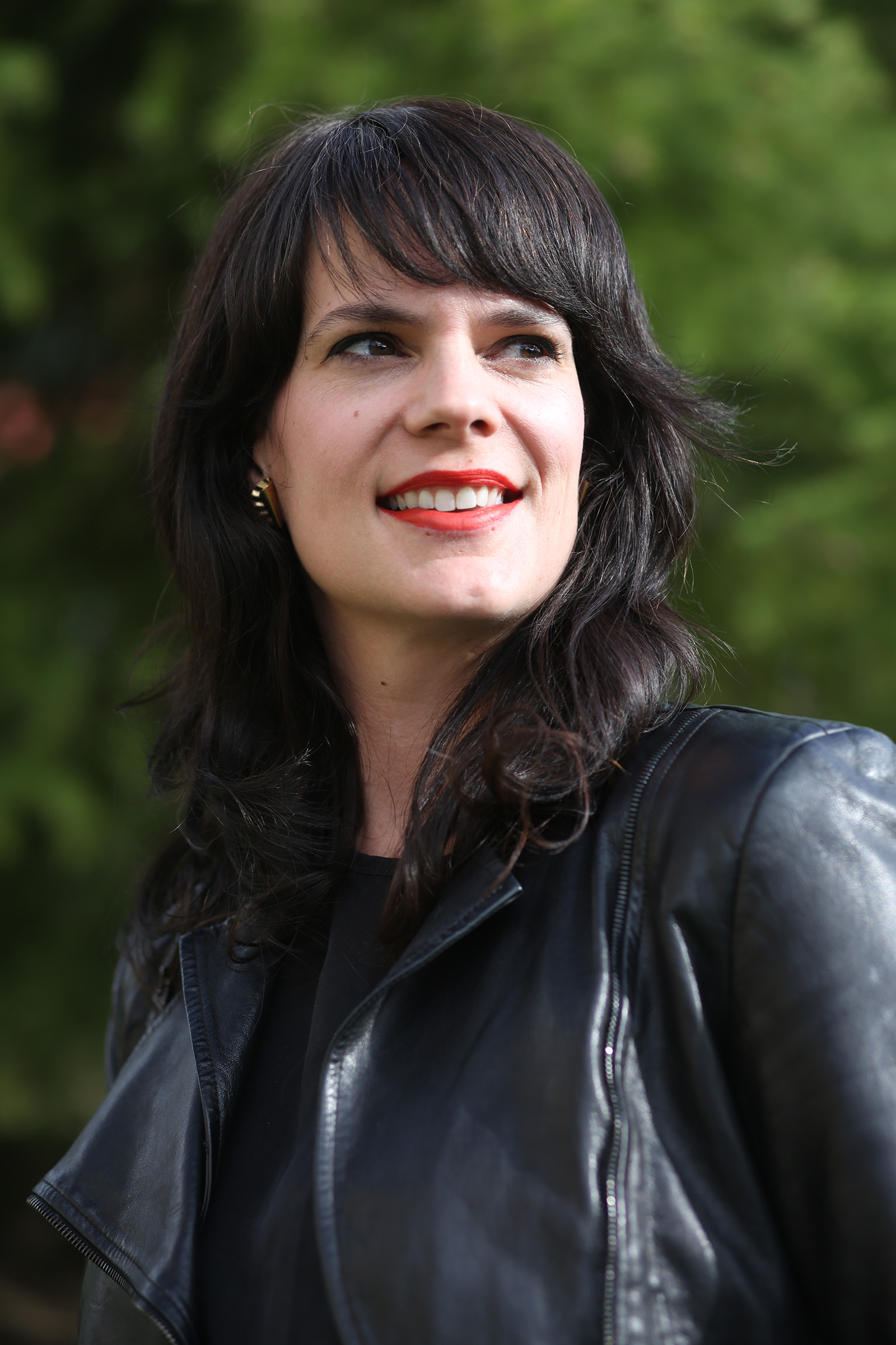 photo of author Elizabeth Cline, a white woman with shoulder-length, dark brown hair, standing outside wearing a red lipstick, a black leather jacket and t-shirt, smiling and looking to the side.