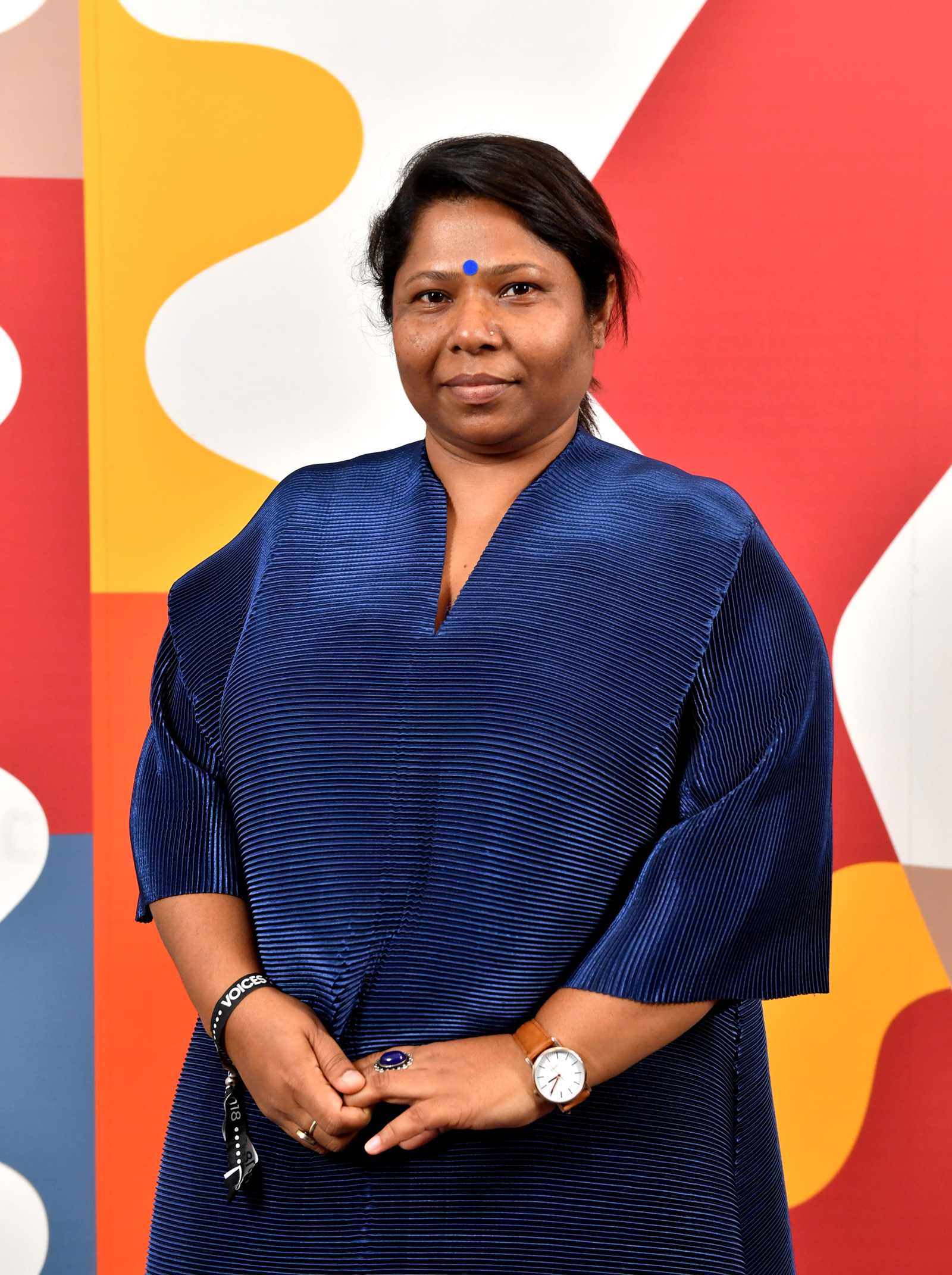 photo of Kalpona Akter, a Bangladeshi activist and cofounder, standing in front of a colorful mural, wearing a navy sheath dress with her hands folded in front of her.