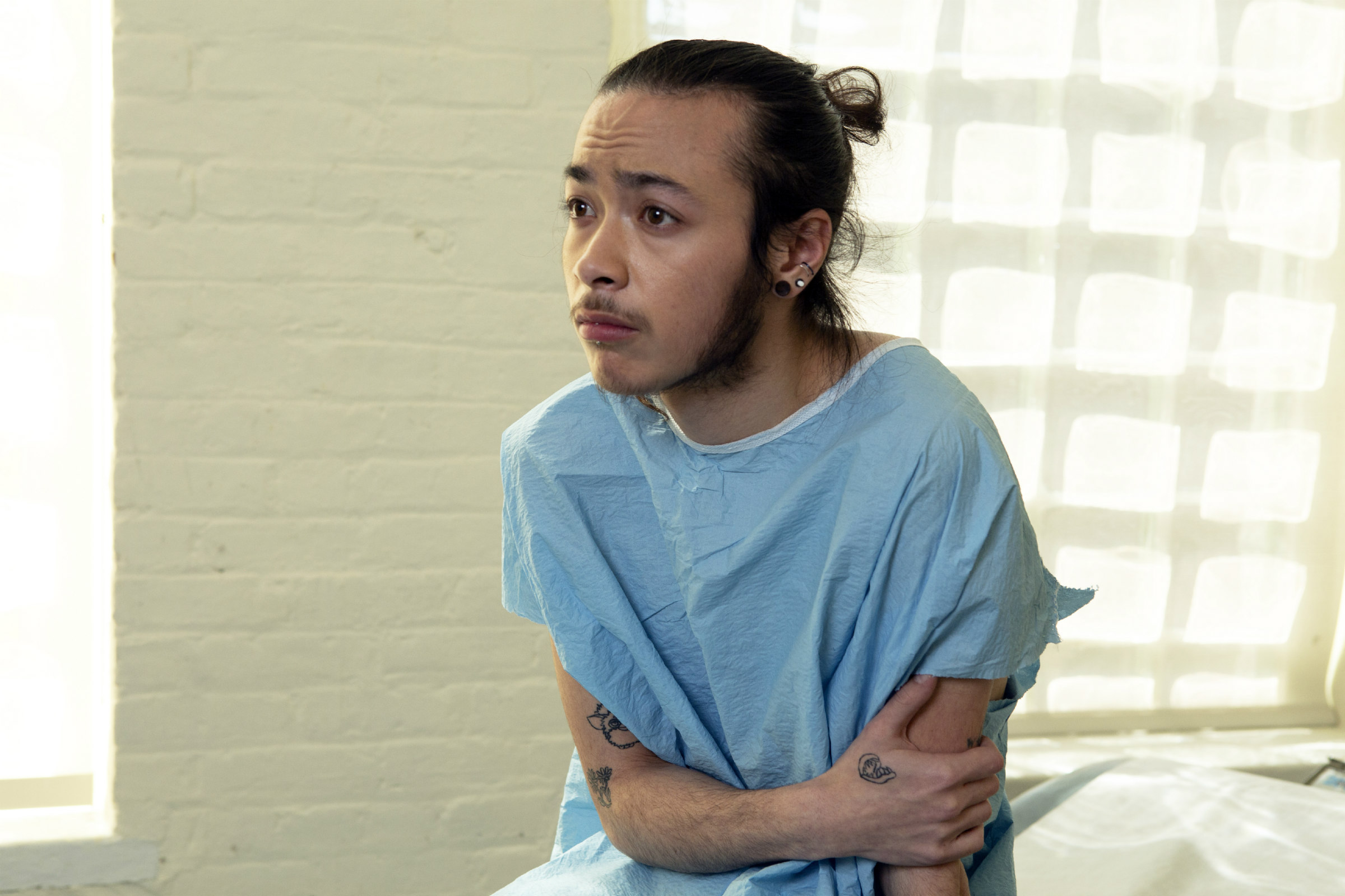 A genderqueer person in a hospital gown with their black hair pulled in a ponytail sits in an exam room looking worried